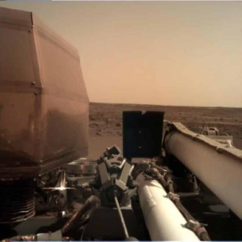 """Após pousar em Marte nesta segunda-feira (26), a sonda Mars Insight, da Nasa, conseguiu transmitir uma foto nítida da superfície de Marte e emitiu sinais que indicam que os painéis solares estão abertos e coletando a luz do Sol na superfície do planeta vermelho. Segundo a Nasa, isso significa que a espaçonave poderá recarregar as baterias todos os dias, o que é crucial para a missão, que deverá medir abalos sísmicos em Marte. Já a foto foi feita por uma câmera instalada no braço robótico. Nova sonda em Marte vai fazer uma espécie de 'ultrassom' do planeta """"A equipe da InSight pode ficar um pouco mais tranquila sabendo que as matrizes solares estão sendo implantadas e recarregando as baterias"""", disse Tom Hoffman, gerente de projeto da InSight no Laboratório de Propulsão a Jato da NASA em Pasadena, Califórnia, que lidera a missão. """"Tem sido um longo dia para a equipe. Mas amanhã começa um excitante novo capítulo para o InSight: operações de superfície e o início da fase de implantação do instrumento"""", disse. A Insight tem um par de placas solares, com 2,2 metros de comprimento cada uma. Quando abertos, diz a Nasa, ficam do tamanho de um carro conversível dos anos 1960. Em Marte, a luz solar é mais fraca se comparada àquela captada na Terra, porque o planeta vermelho está mais distante do Sol. Entretanto, segundo a agência espacial americana, a sonda está preparada para este cenário: ela produz de 600 a 700 watts em um dia claro, o suficiente para manter os instrumentos operando no planeta. Ainda que a poeira cubra os painéis, o sistema continuará produzindo pelo menos de 200 a 300 watts. Primeira imagem enviada pela sonda Insight de Marte — Foto: Nasa/via AP Primeira imagem enviada pela sonda Insight de Marte — Foto: Nasa/via AP Primeira imagem enviada pela sonda Insight de Marte — Foto: Nasa/via AP Próximos passos Nos próximos dias, a equipe da missão vai ativar o braço robótico da InSight e usar a câmera acoplada para tirar fotos do solo. Com essas informações, os e"""